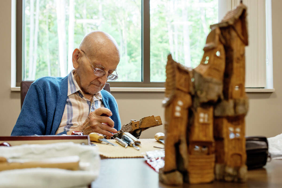 Bill Stasinski works on a wood carving in his signature style, which features miniature houses stacked upon one another, during a regular gathering of wood carvers Tuesday, Sept. 7, 2021 at Senior Services of Midland County's Sanford Activity & Dining Center. (Katy Kildee/kkildee@mdn.net)