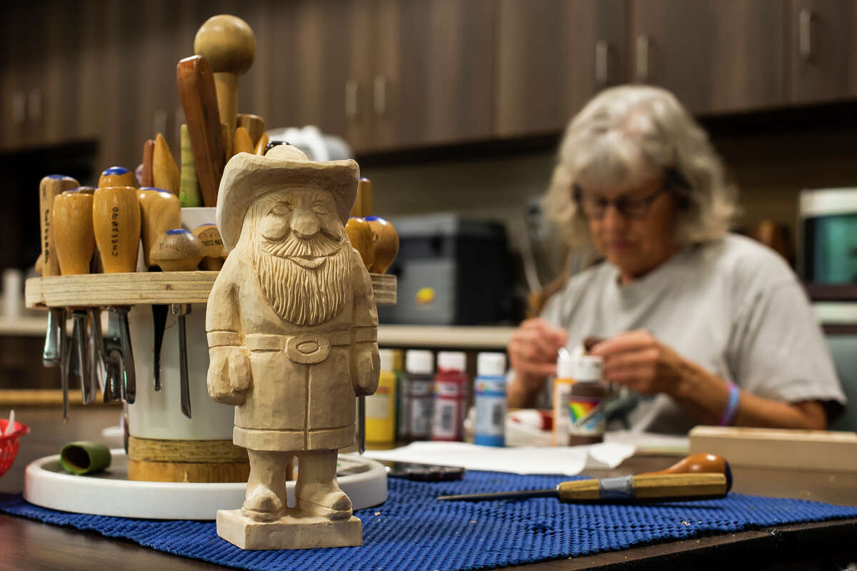 Margaret Wilson, right, works on a wood carving while a piece by Carol Cheesbro, left, is displayed on the table during a regular gathering of wood carvers Tuesday, Sept. 7, 2021 at Senior Services of Midland County's Sanford Activity & Dining Center. (Katy Kildee/kkildee@mdn.net)