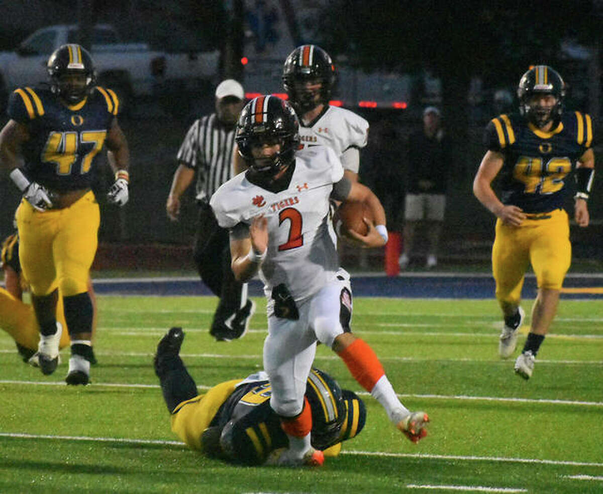 Edwardsville quarterback Jake Curry attempts to elude an O'Fallon defender in the backfield during the first quarter on Friday in O'Fallon.