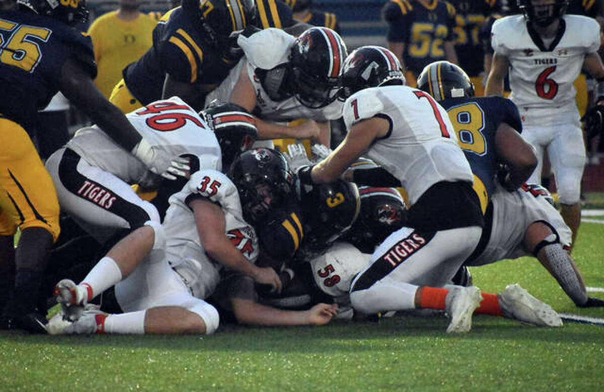 The Edwardsville defense makes a gang tackle in the first quarter on Friday in O'Fallon.