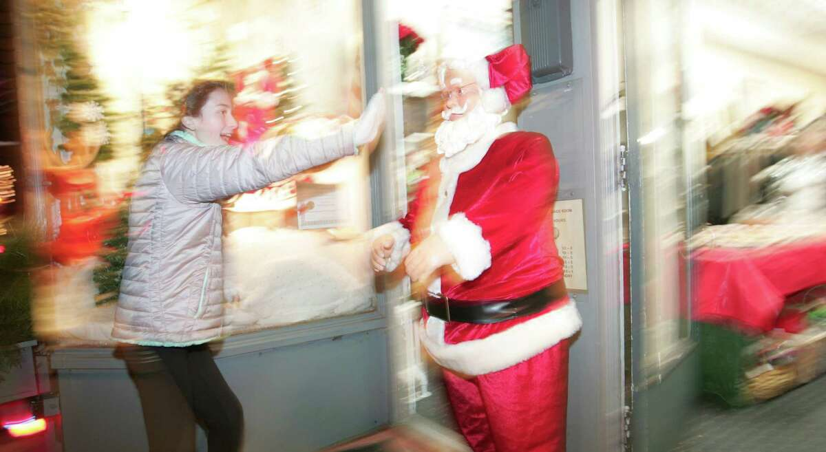 A young girl high fives Santa as hundreds of area residents enjoy Old Greenwich First Light in 2015. The event is slated to return on Dec. 4.