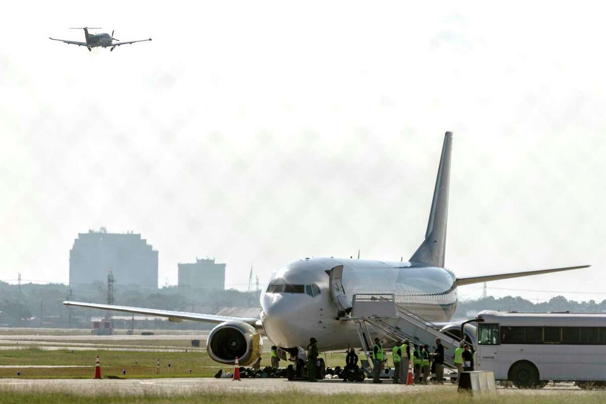 An airplane scheduled to fly to Port-au-Prince, Haiti, waits Monday at San Antonio International Airport for migrants to board.