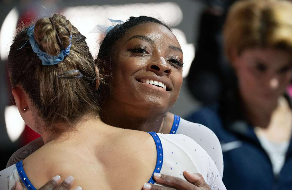 05 October 2019, Baden-Wuerttemberg, Stuttgart: Gymnastics: world championship, qualification, women. Simone Biles from the USA embraces a team mate after her practice on uneven bars. Photo: Marijan Murat/dpa (Photo by Marijan Murat/picture alliance via Getty Images)