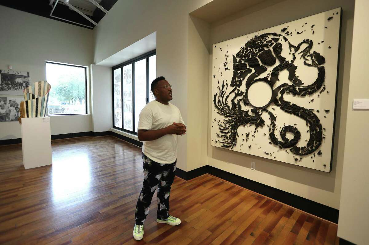 """Harrison Guy, Director of Arts and Culture at Fifth Ward Community Redevelopment Corporation looks at Mel Chin's """"Wheel of Death"""" piece as he walked through the """"Art For The People"""" exhibit, celebrating the 50th anniversary of """"The De Luxe Show"""", which was the first racially integrated art show in American history, in 1971. The exhibition is a look back at the original exhibition through Menil Collection photographs at The Deluxe Theater at 3303 Lyons Avenue, Tuesday, September 21, 2021, in Houston."""