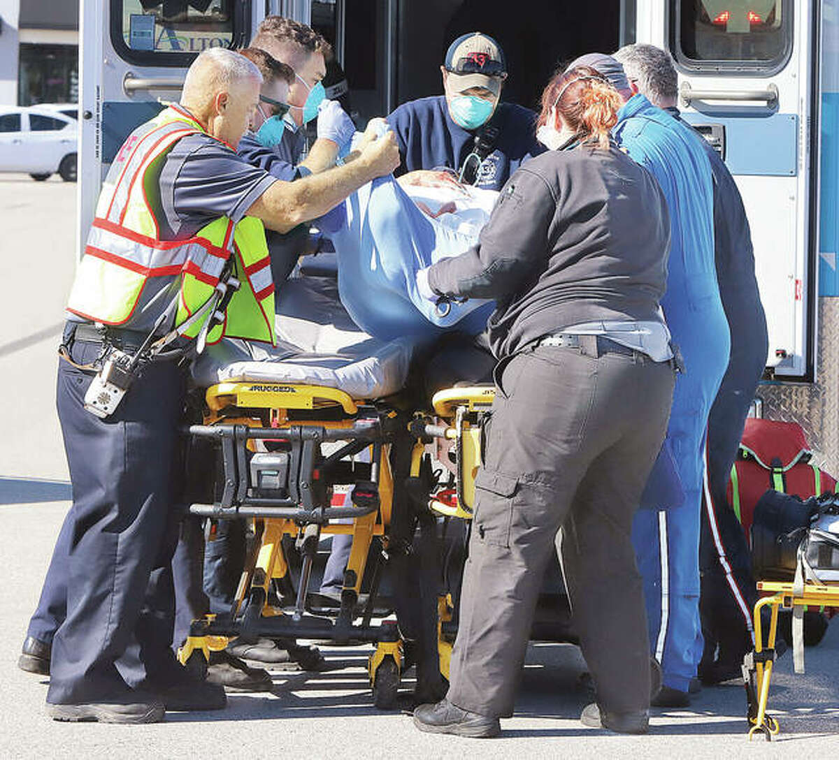 East Alton firefighters and Alton Memorial Ambulance paramedics help ARCH helicopter flight nurses transfer a man to the helicopter's stretcher Thursday in the Eastgate Plaza parking lot after a tree limb being cut off fell on the man in the 100 block of Irwin Street in East Alton.