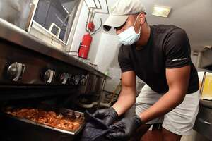 Josh Watkins, executive director of the Community Soup Kitchen, checks on sweet chili chicken wings being prepared for the Keefe Center in Hamden at the Community Soup Kitchen in New Haven on Sept. 22, 2021.