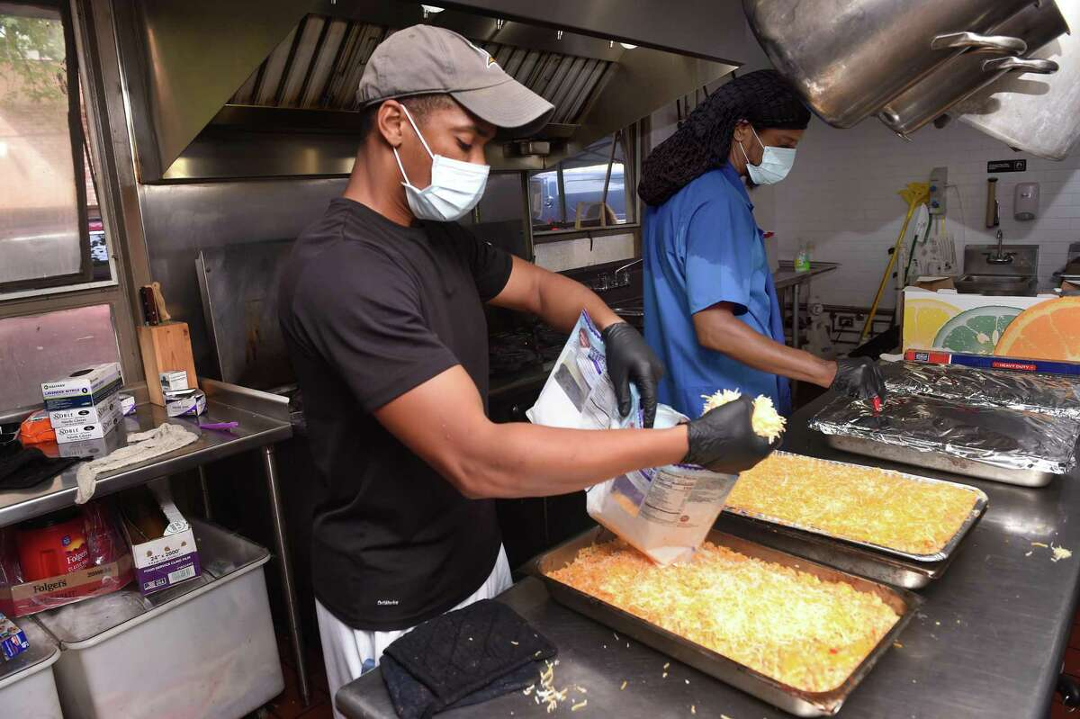 Josh Watkins (left), executive director of the Community Soup Kitchen, and kitchen manager Winston Sutherland prepare macaroni and cheese for the Keefe Center in Hamden at the Community Soup Kitchen in New Haven on Sept. 22, 2021.