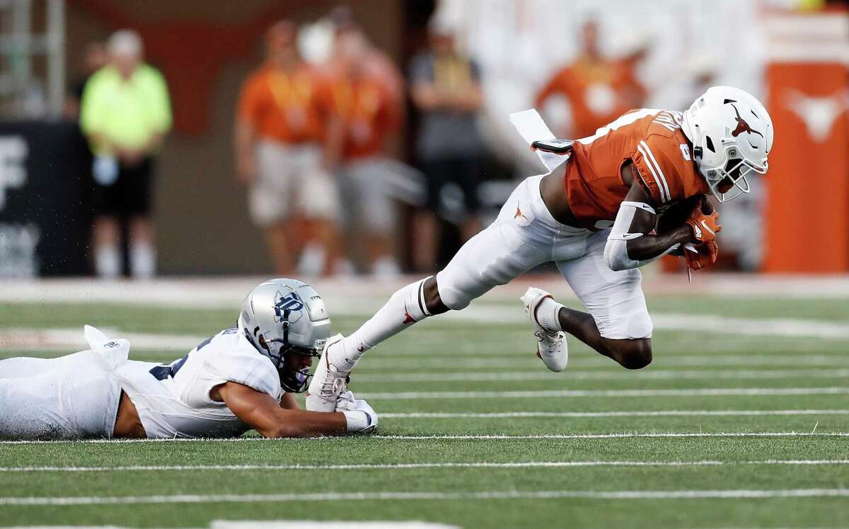 AUSTIN, TEXAS - SEPTEMBER 18: Xavier Worthy #8 of the Texas Longhorns is tripped up by Gabe Taylor #26 of the Rice Owls in the first half at Darrell K Royal-Texas Memorial Stadium on September 18, 2021 in Austin, Texas. (Photo by Tim Warner/Getty Images)