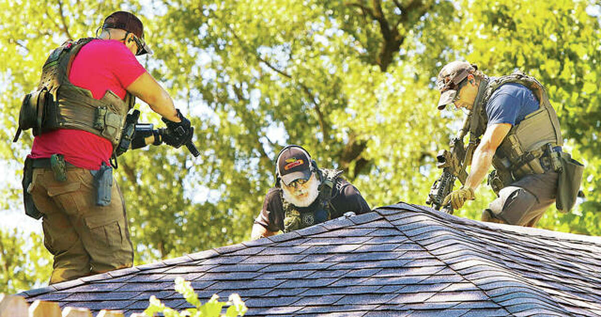 U.S. Marshals point guns toward a hole being cut in the roof of a house in the 400 block of East 9th Street in Alton Thursday where a subject was hiding from arrest. After the hole was cut, the man surrendered to officers inside the house. More photos appear at thetelegraph.com.