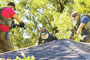 U.S. Marshals point guns toward a hole being cut in the roof of a house in the 400 block of East 9th Street in Alton Thursday where a subject was hiding from arrest. After the hole was cut, the man surrendered to officers inside the house.