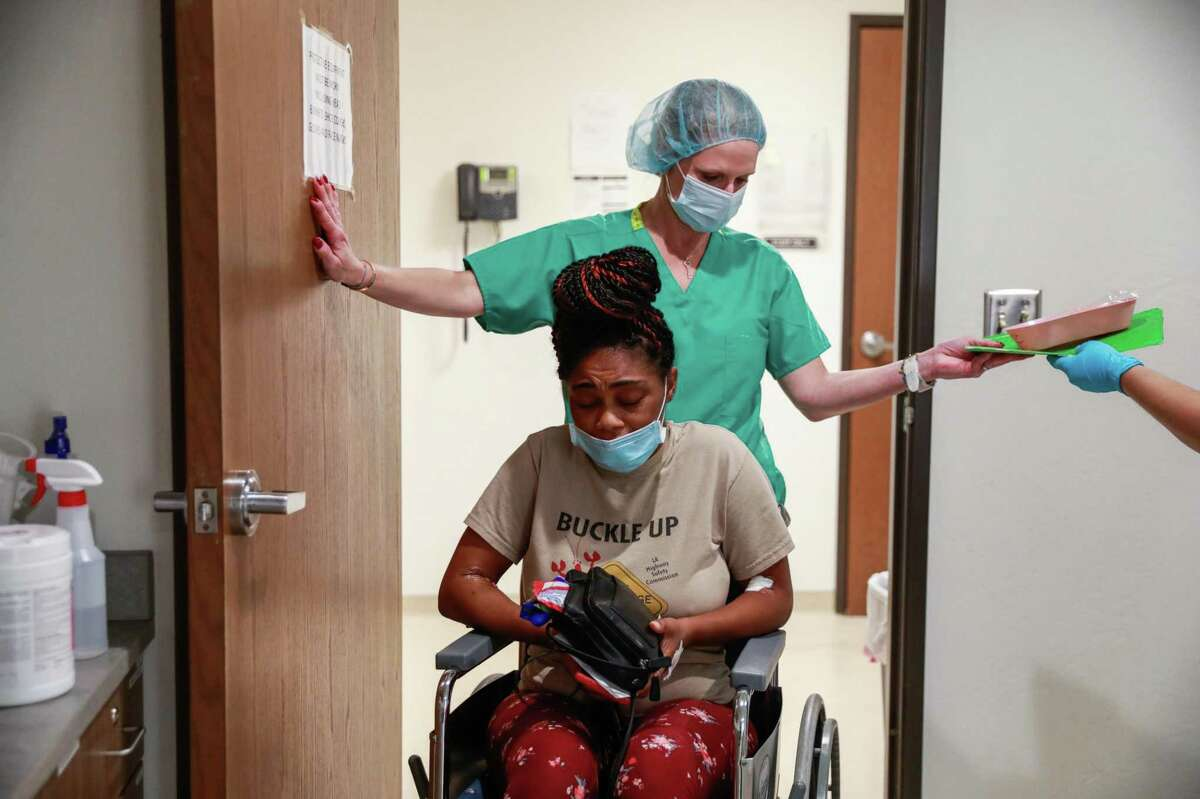 """Volunteer Jennifer Goodner helps patient Judith, 33, in a wheelchair after a surgical abortion at the Trust Women clinic in Oklahoma City. Judith had to travel more than six hours from Houston to get the procedure. Judith suffers from Type 1 diabetes and her partner, with whom she shares four kids, suffers from kidney failure. """" I am sick. Why would I want to bring kids into this world? I know that if I'm gone no one can mother them like I do,"""" she said."""