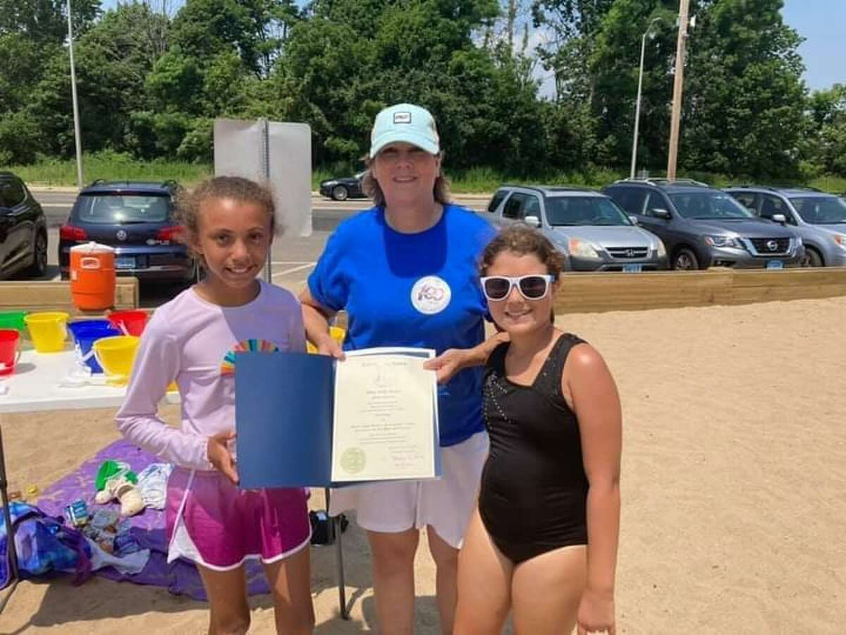 """Samantha Boyd, left, and Brooklyn Loehfelm, both 10, receive a mayoral citation for their winning sand sculpture, """"Shelltown,"""" from city Youth and Family Services Director Diane Dietman during the West Haven Centennial Celebration's Summer Sandcastle Contest at Sea Bluff Beach on July 17"""