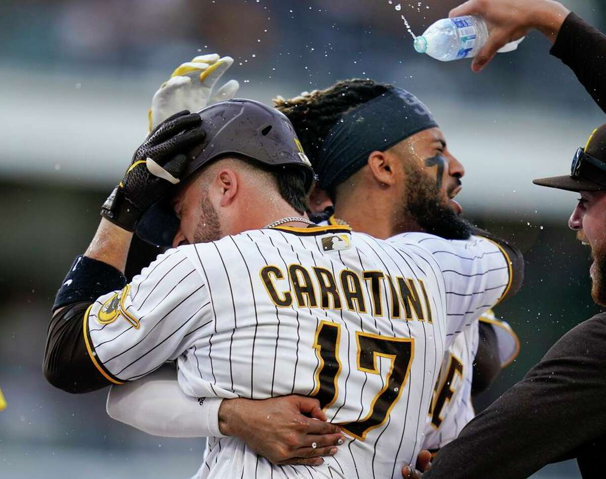 The Padres' Victor Caratini (17) is besieged by teammates after his single drove in the winning run in the 10th inning.