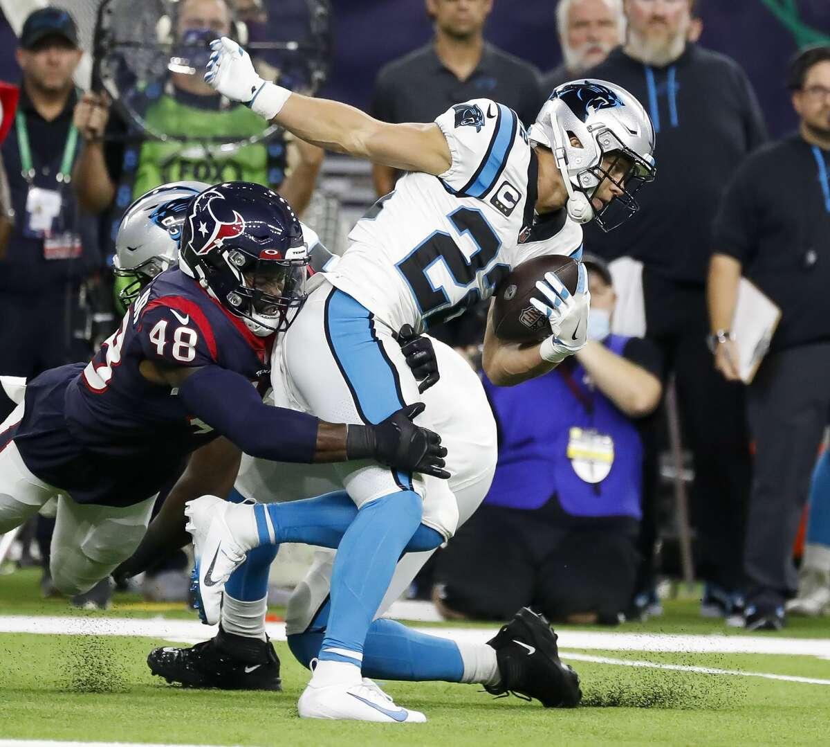 Carolina Panthers running back Christian McCaffrey (22) tries to run through Houston Texans linebacker Joe Thomas (48) during the first quarter of an NFL football game at NRG Stadium, Thursday, September 23, 2021, in Houston.