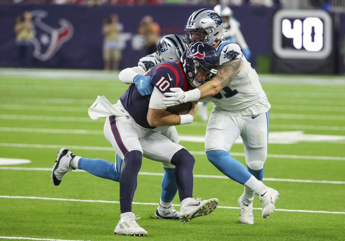 Houston Texans quarterback Davis Mills (10) is sacked by Carolina Panthers linebacker Haason Reddick (43) and defensive end Morgan Fox (91) during the first quarter of an NFL football game Thursday, Sept. 23, 2021, in Houston.