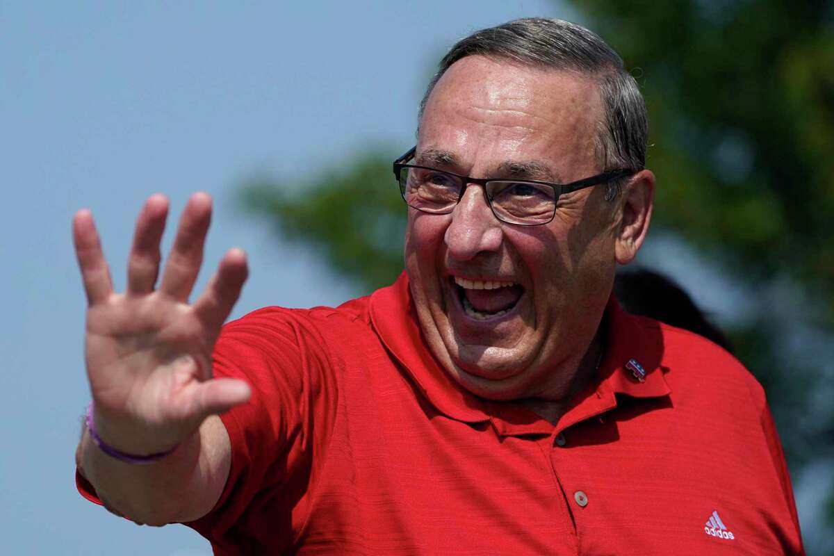 Former Maine Gov. Paul LePage, a Republican gubernatorial candidate, waves while marching in the State of Maine Bicentennial Parade, on Aug. 21 in Lewiston, Maine.
