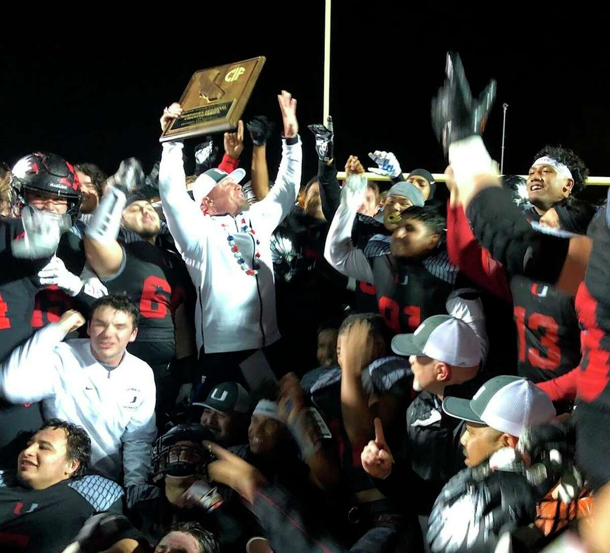 Clayton Valley-Concord players and coach Tim Murphy celebrate their 2019 Northern Califiornia 2-AA title.