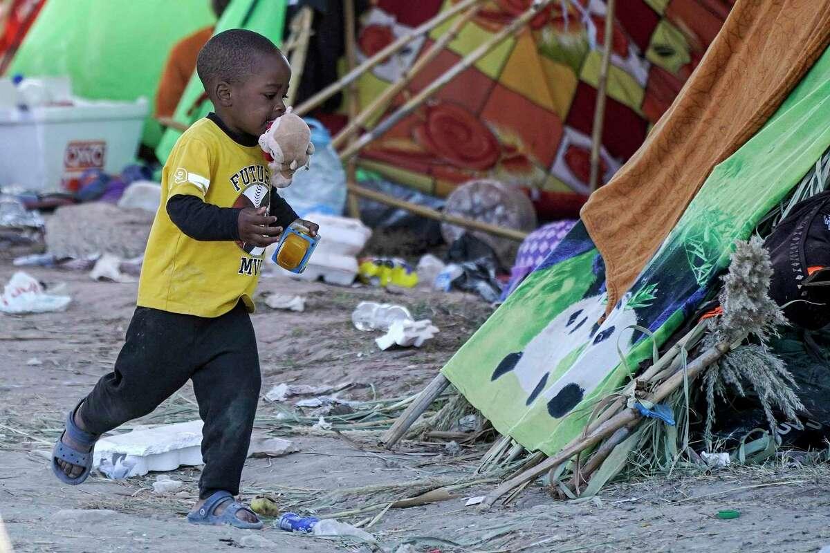 Un niño corre con comida que recibió de voluntarios en un campamento debajo del Puente Internacional Del Río donde se han alojado migrantes, muchos de Haití, después de cruzar el río Bravo, el jueves 23 de septiembre de 2021, en Del Río, Texas.