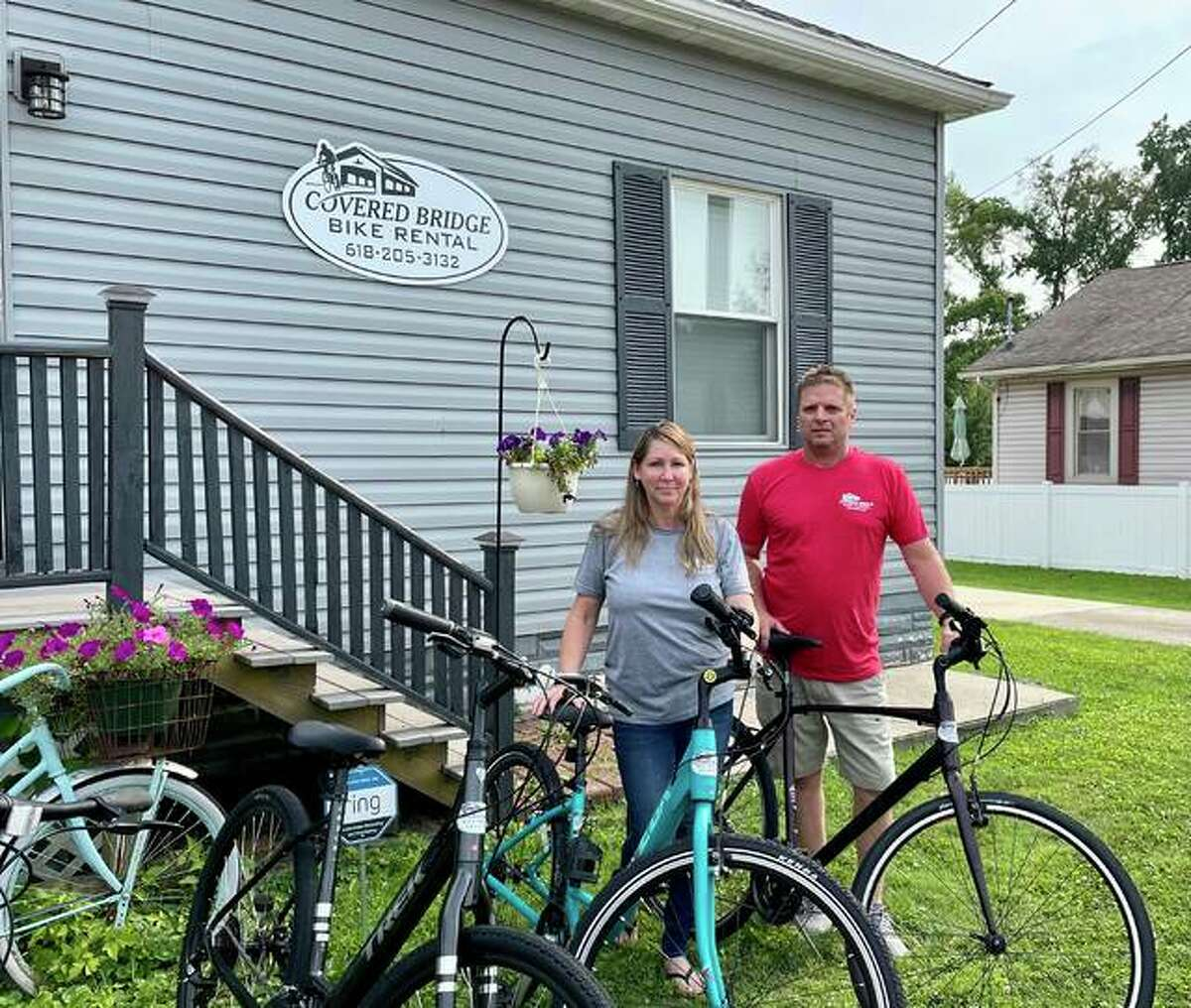 Owners of Covered Bridge Bike Rental Teri and Chris Moore stand in front of their new store front with a couple of their rental bikes. They have 4 Class 2 e-bikes for rent.