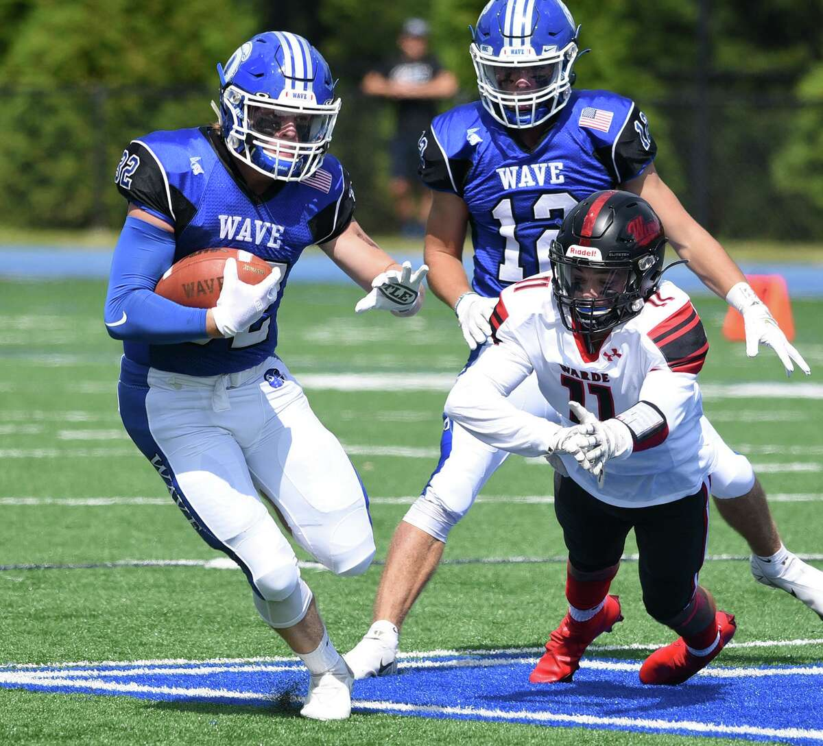 Darien's Tighe Cummiskey (32) runs with the ball as Warde's Lucas Coleman (11) dives to slow him down during a football game at Darien High School on Sat., Sept. 11, 2021.