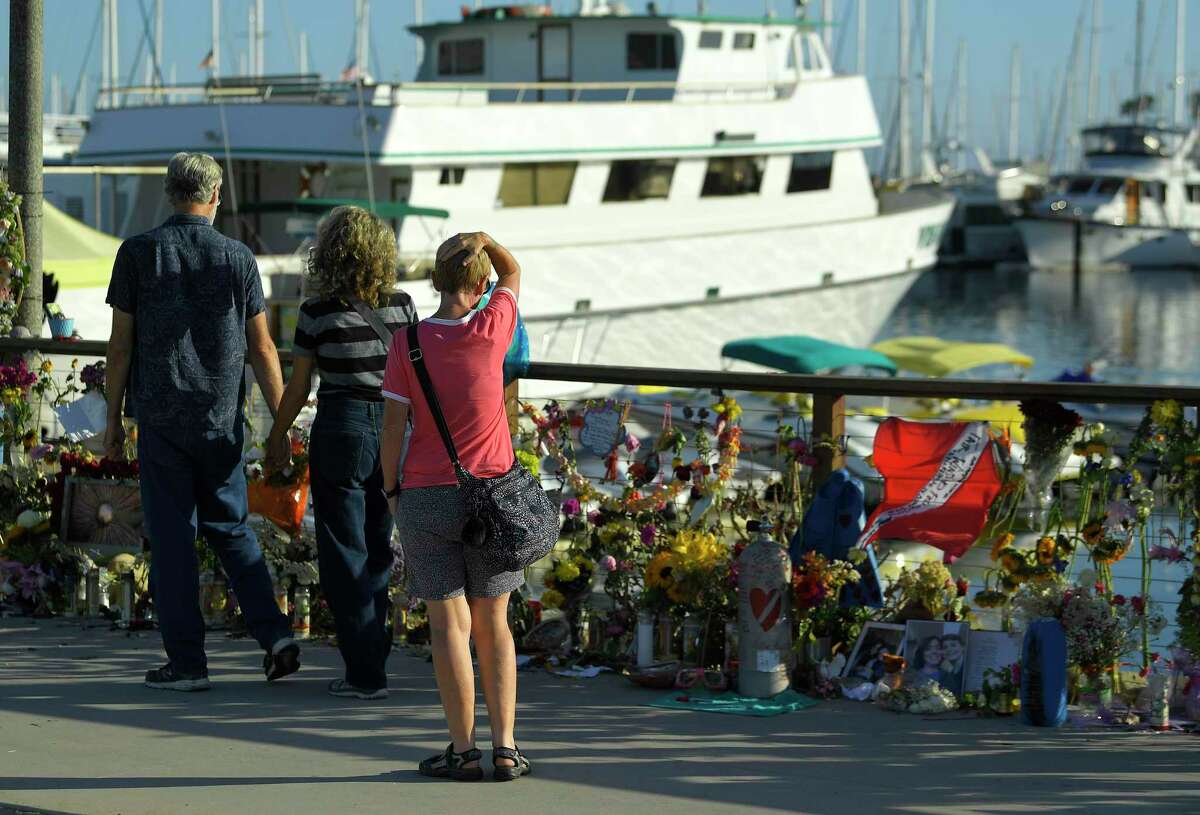This file photograph shows people visiting a memorial to the victims who died aboard the dive boat Conception as its sister boat Vision sits in the background Friday, Sept. 6, 2019, in Santa Barbara, Calif.