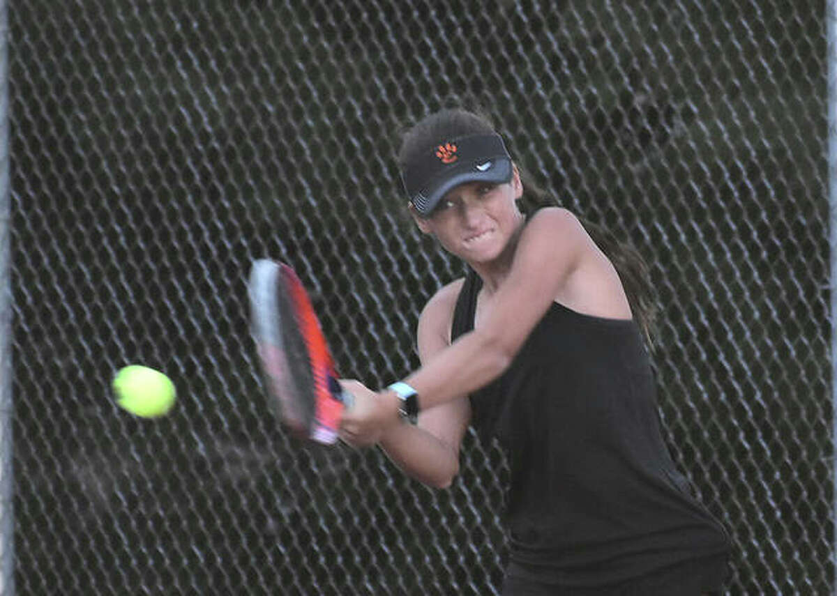 Edwardsville's Sophie Byron smashes a backhand shot during her singles match against Belleville West on Thursday inside the EHS Tennis Center.
