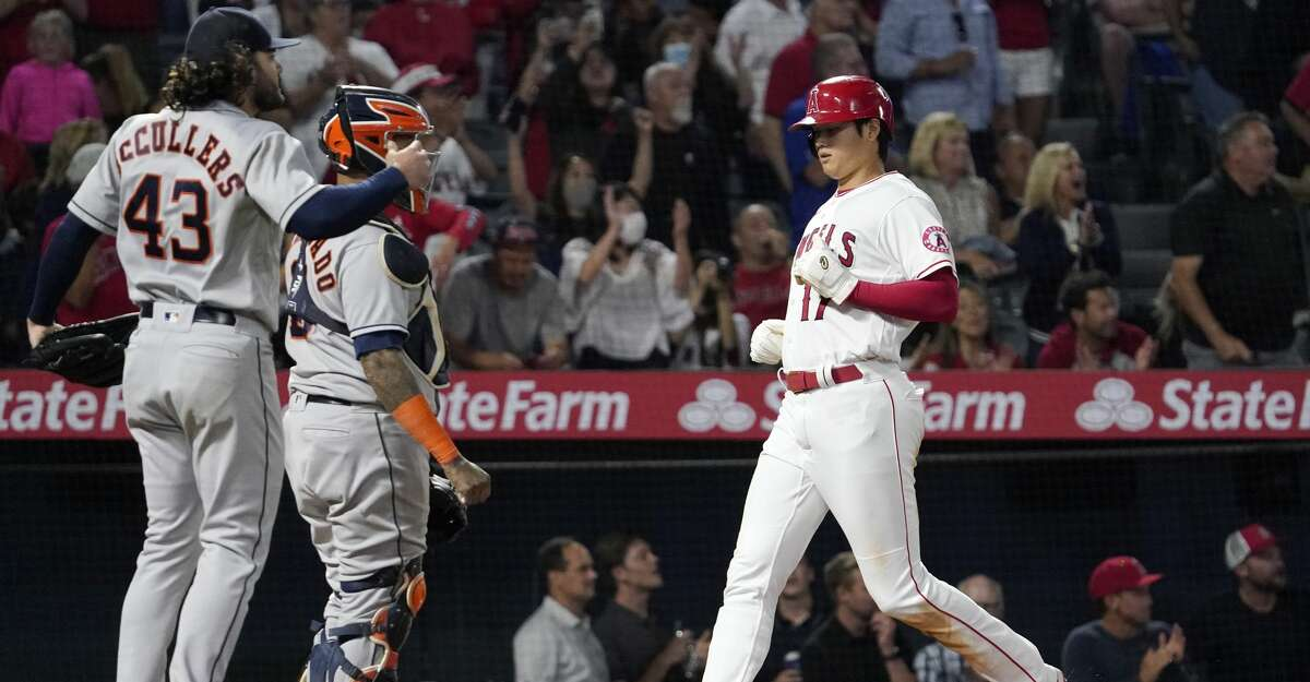 Los Angeles Angels designated hitter Shohei Ohtani, right, scores on a double by Jack Mayfield as Houston Astros starting pitcher Lance McCullers Jr., left, and catcher Martin Maldonado watch during the sixth inning of a baseball game Thursday, Sept. 23, 2021, in Anaheim, Calif. (AP Photo/Mark J. Terrill)