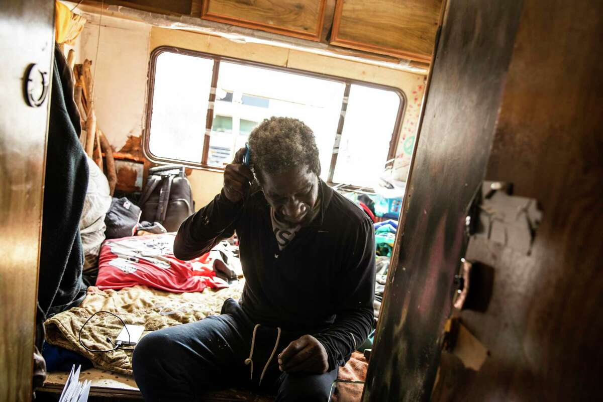 James Keys, 59, brushes his hair after waking up inside his RV parked along Hunters Point Expressway in San Francisco.