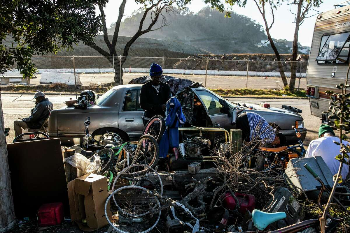 James Keys (center) has been living out of his car and an RV parked along Hunters Point Expressway for about a year.