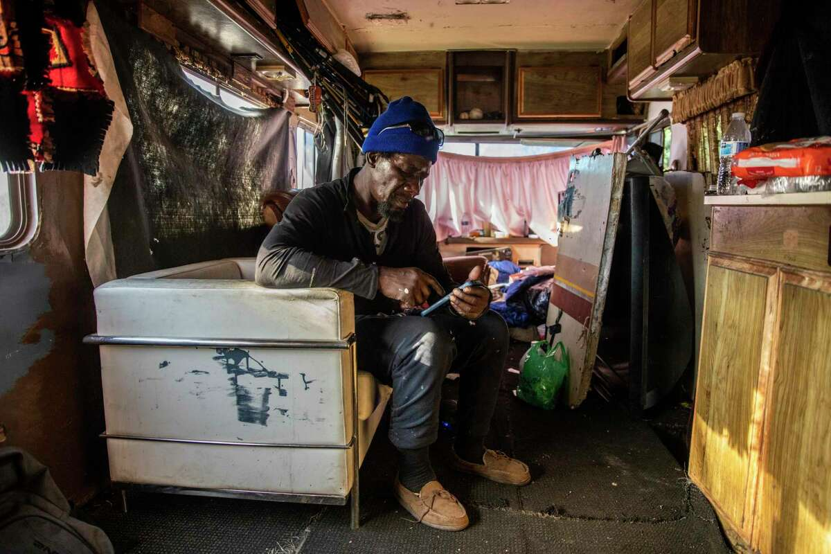 James Keys checks his phone inside his RV parked along Hunters Point Expressway in San Francisco.