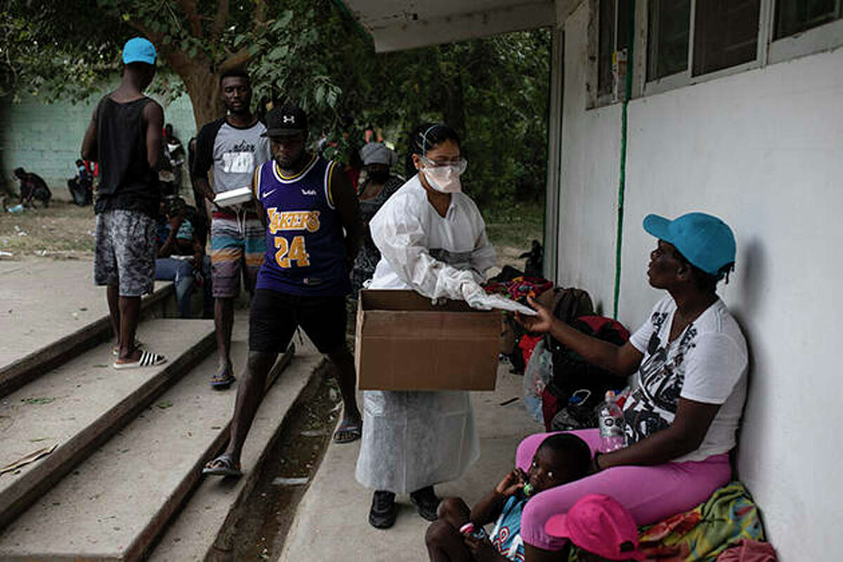 A nurse hands out masks Tuesday at an improvised refugee camp in Ciudad Acuña, Mexico. The options remaining for thousands of Haitian migrants straddling the Mexico-Texas border are narrowing as the U.S. government ramps up to an expected six expulsion flights to Haiti. Mexico, meanwhile, began busing some away from the border.
