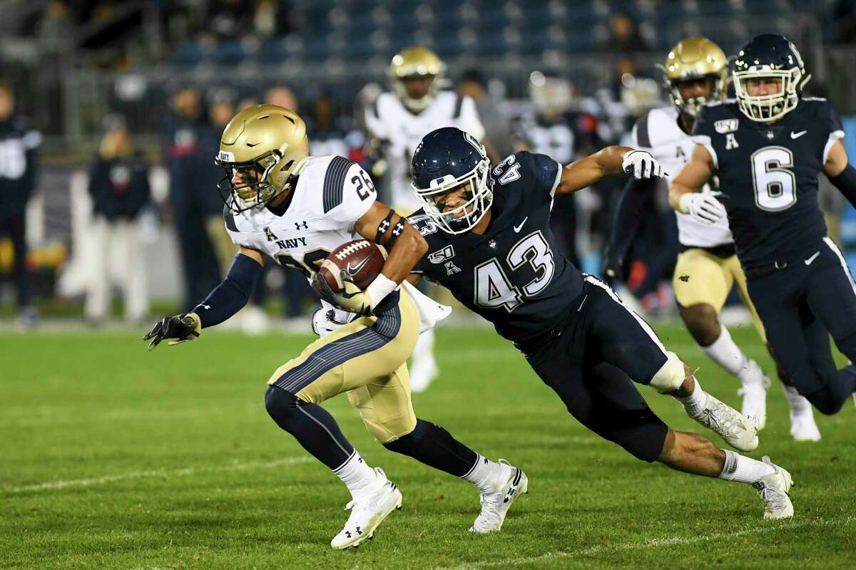 Navy wide receiver Garrett Winn (26) is chased down by Connecticut linebacker Jackson Mitchell (43) during the second half of an NCAA college football game Friday, Nov. 1, 2019, in East Hartford, Conn. (AP Photo/Stephen Dunn)