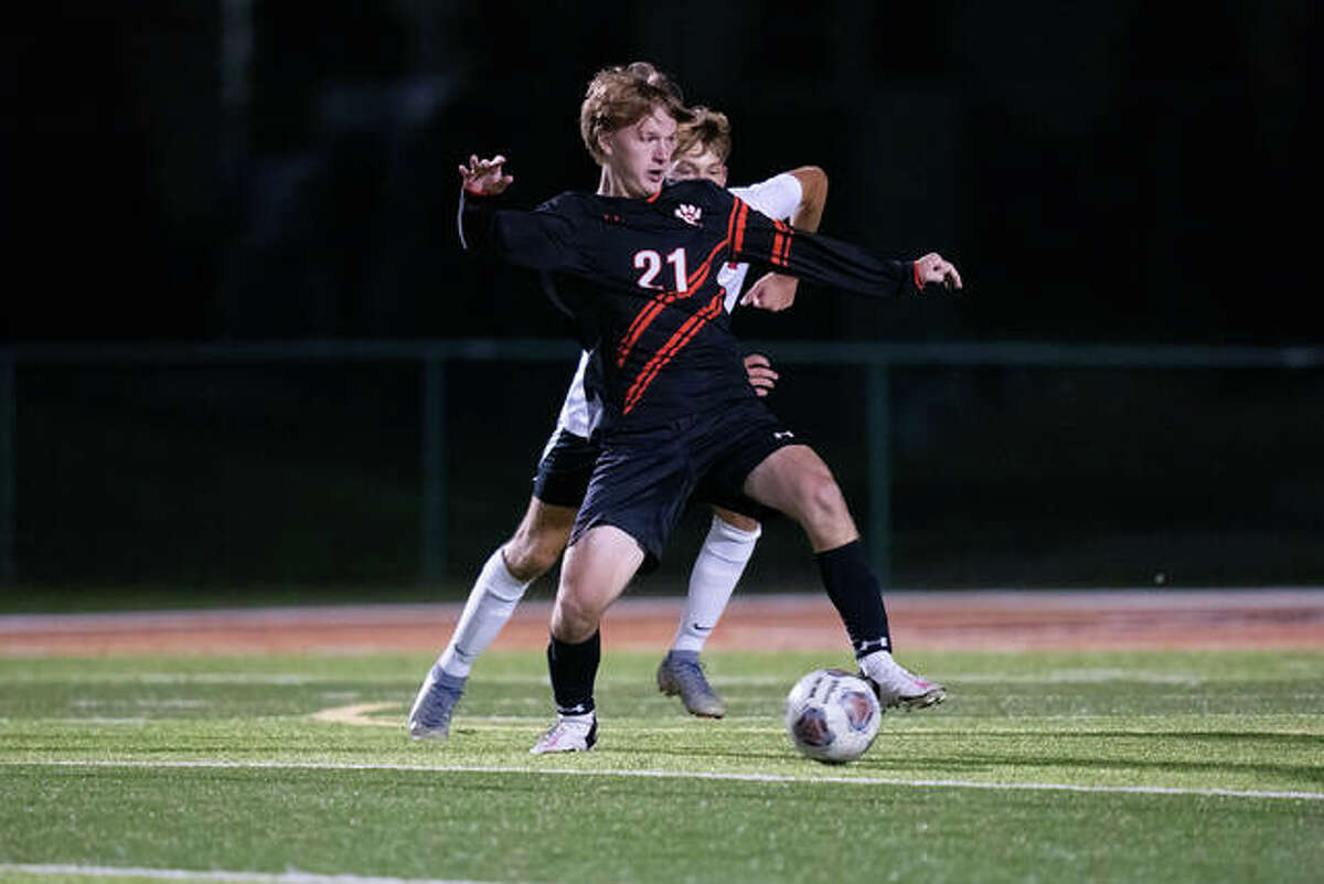 Edwardsville's Evan Moore shields the ball away from an Alton defender during Thursday's game inside the District 7 Sports Complex in Edwardsville.