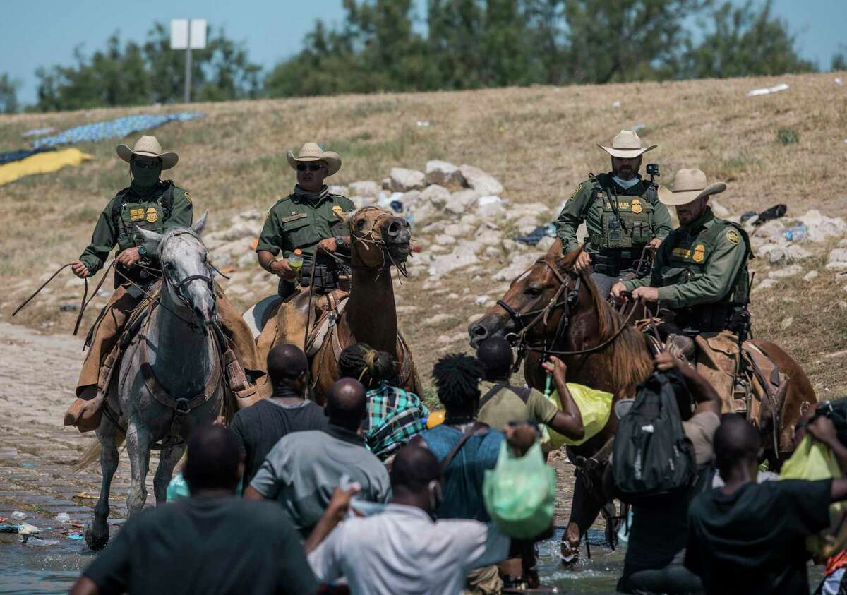 U.S. Customs and Border Protection mounted officers attempt to contain migrants as they cross the Rio Grande from Ciudad Acuña into Del Rio on Sept. 19. Thousands of Haitian migrants have been arriving to Del Rio as authorities attempt to close the border to stop the flow of migrants.