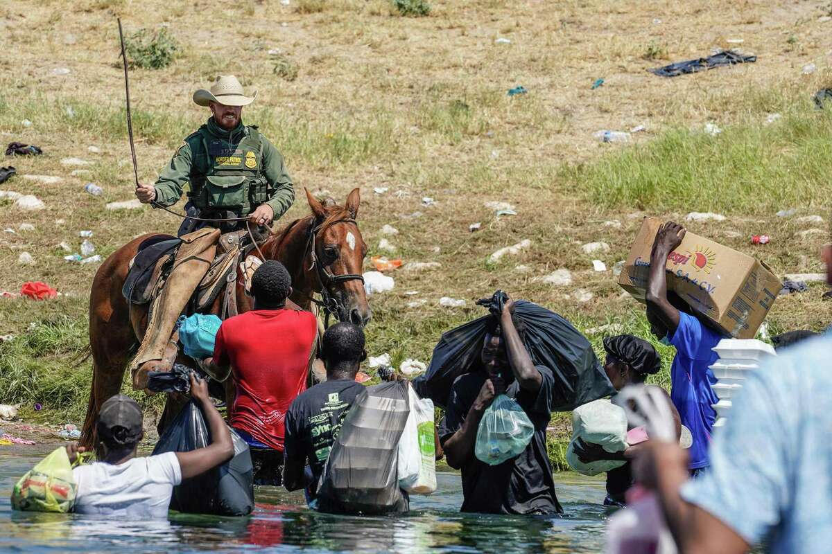 A U.S. Border Patrol agent on horseback raises his reins as he tries to stop Haitian migrants from entering an encampment on the banks of the Rio Grande near the Acuña Del Rio International Bridge in Del Rio on Sept. 19.