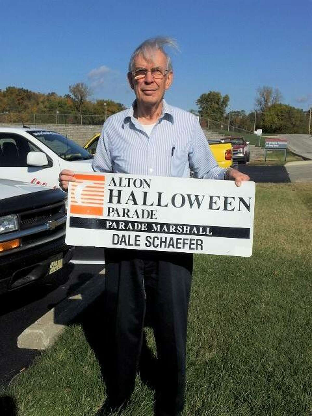 Dale Schaefer, of Godfrey, holds the sign for the car he rode in as parade marshal in 2013 for the East End Improvement Association's annual Alton Halloween Parade. Schaefer, 85, died Wednesday afternoon; he was the second longest-serving member of the EEIA.