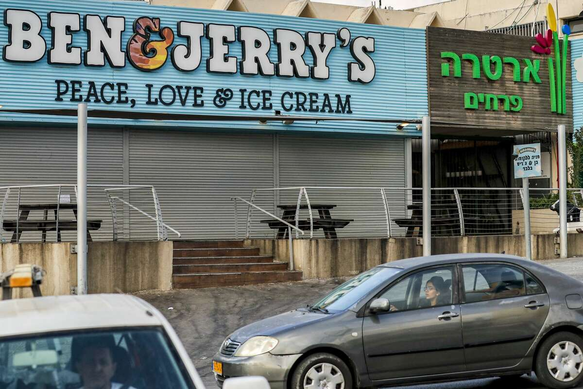 """Motorists drive past a closed """"Ben & Jerry's"""" ice-cream shop in the Israeli city of Yavne, about 30 kilometres south of Tel Aviv, on July 23, 2021. - On July 19, Vermont-based Ben & Jerry's announced it would no longer sell its ice cream in the Israeli-occupied Palestinian territories, namely the West Bank and East Jerusalem, which have been under control of the Jewish state since 1967."""