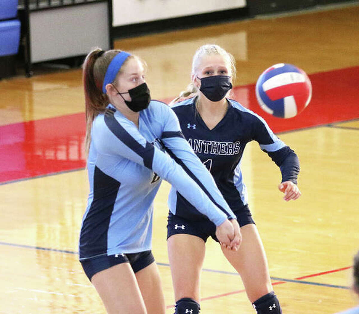 Jersey's Kendal Davis (left) receives a serve in front of libero Sammie Malley during a match at the Roxana Tourney in August. On Thursday, the Panthers dropped a MVC match to Triad in Jerseyville.
