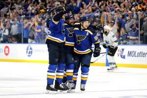 David Perron #57 of the St. Louis Blues celebrates with Colton Parayko #55 and Vladimir Tarasenko #91 after scoring his second goal in an NHL postseason game. (Photo by Elsa/Getty Images)