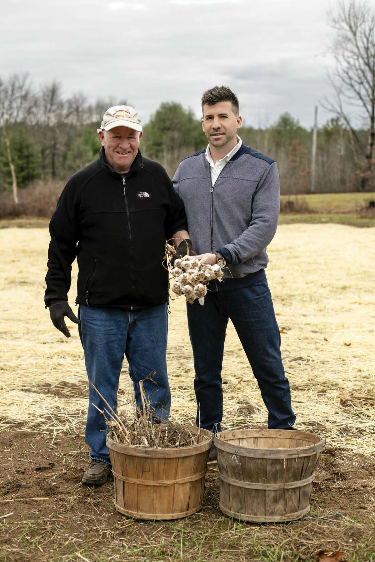 Saratoga Garlic founder Bill Higgins, left, and his son, Max, who now runs the company, show off the signature crowd at their Saratoga County farm.