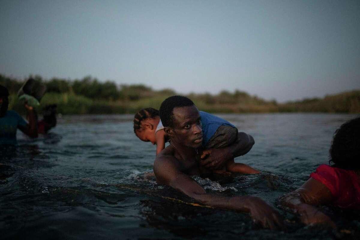 Haitian migrants wade across the Rio Grande Sept. 19. This most recent caravan underscores the urgency for comprehensive immigration reform.