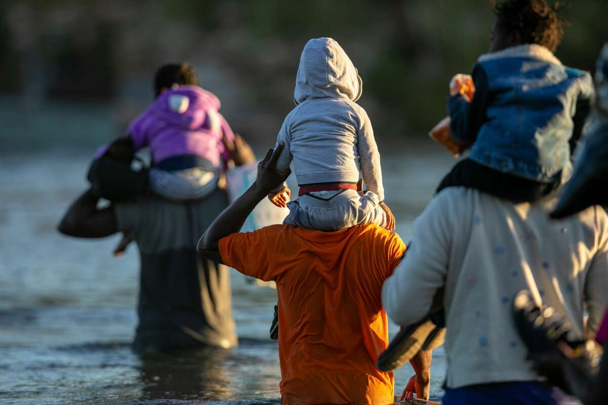 Haitian immigrant families cross the Rio Grande into Del Rio, Texas on September 23, 2021, from Ciudad Acuna, Mexico. (Photo by John Moore/Getty Images)