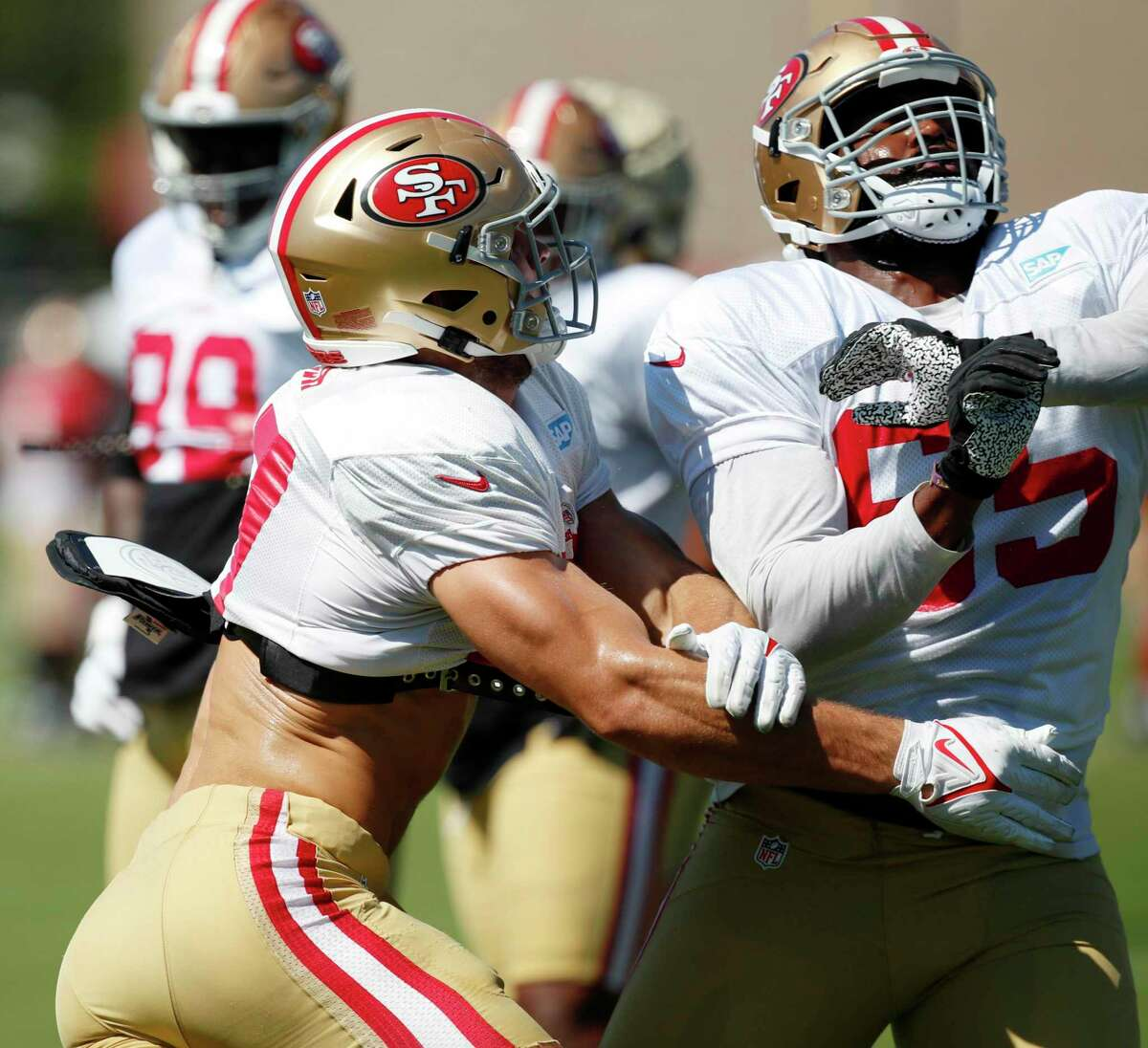 San Francisco 49ers defensive end Nick Bosa works against offensive guard Aaron Banks takes part in drills at an NFL football training camp in Santa Clara, Calif., Tuesday, Aug. 3, 2021.