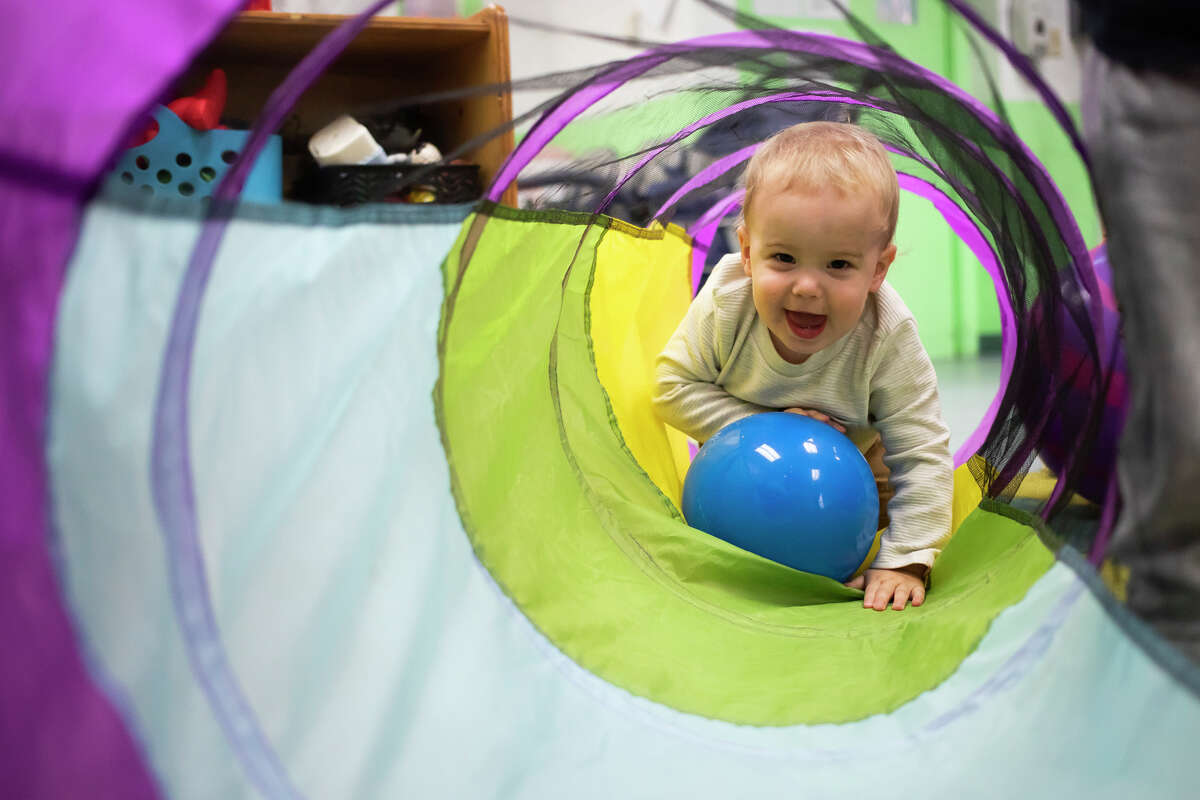Brooks Spoelhof, 1, climbs through a tunnel while playing with other toddlers Thursday, Sept. 23, 2021 at the Greater Midland Community Center's early childhood center in Midland. (Katy Kildee/kkildee@mdn.net)