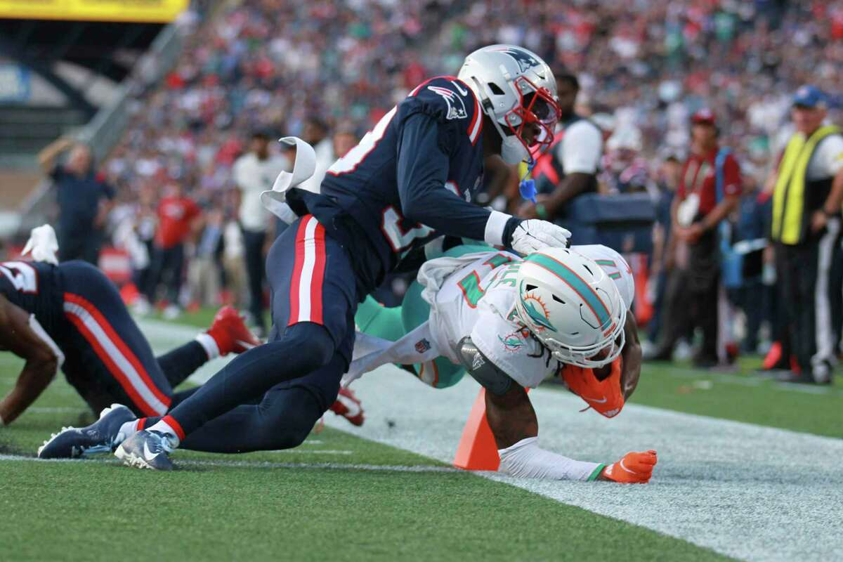 Miami Dolphins wide receiver Jaylen Waddle (17) scores a touchdown as New Englands Patriots cornerback Joejuan Williams (33) attempt to defend on the play during the second half of an NFL football game, Sunday, Sept. 12, 2021, in Foxborough, Mass. (AP Photo/Stew Milne)