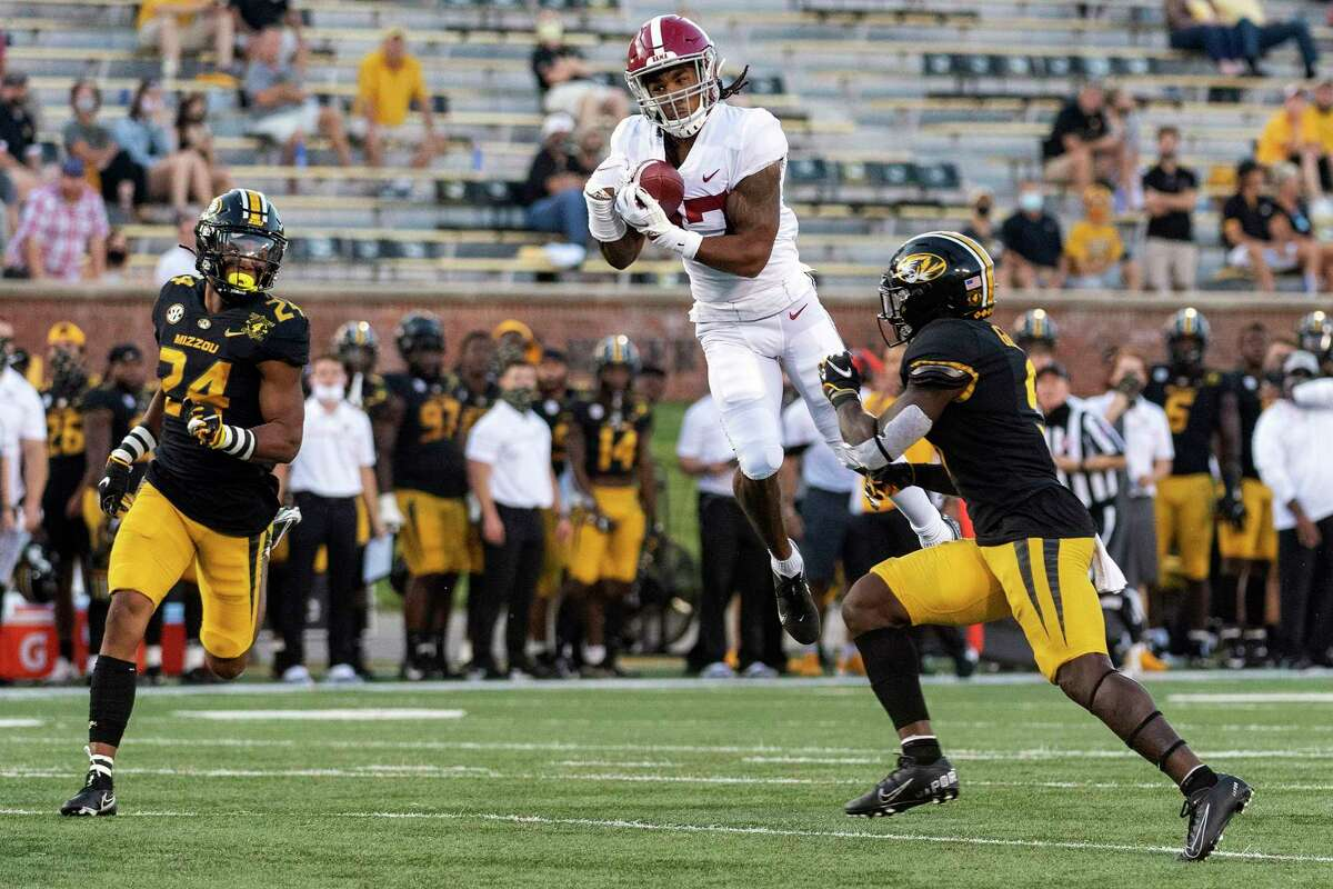 FILE - In this Saturday, Sept. 26, 2020, file photo, Alabama wide receiver Jaylen Waddle, center, pulls down a reception between Missouri's Tyree Gillespie, right, and Ishmael Burdine, left, during the first quarter of an NCAA college football game in Columbia, Mo. (AP Photo/L.G. Patterson, File)