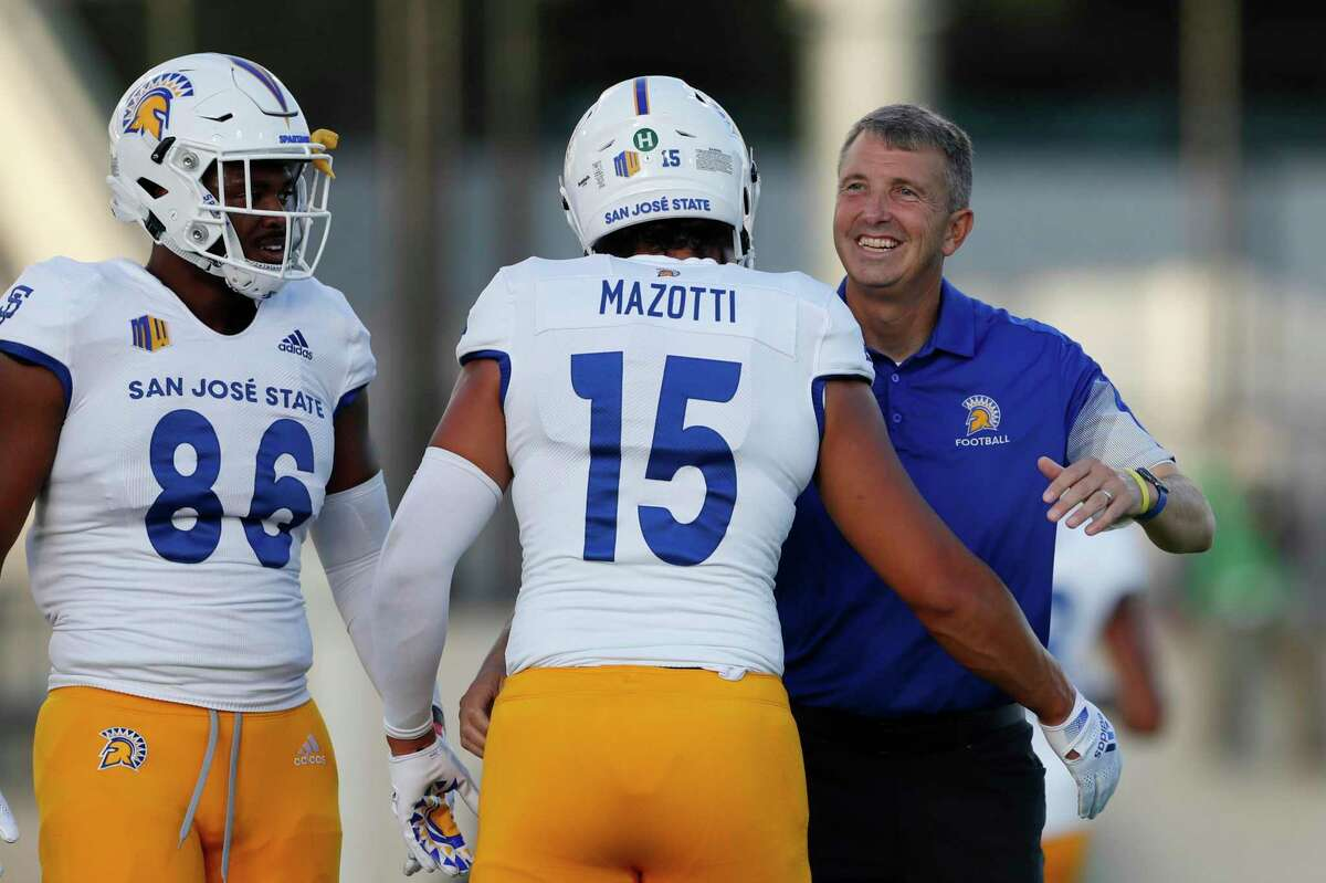 San Jose State head coach Brent Brennan talks with his players before the start of a college football game against Hawaii, Saturday, Sept. 18, 2021, in Honolulu. (AP Photo/Marco Garcia)(AP Photo/Marco Garcia)