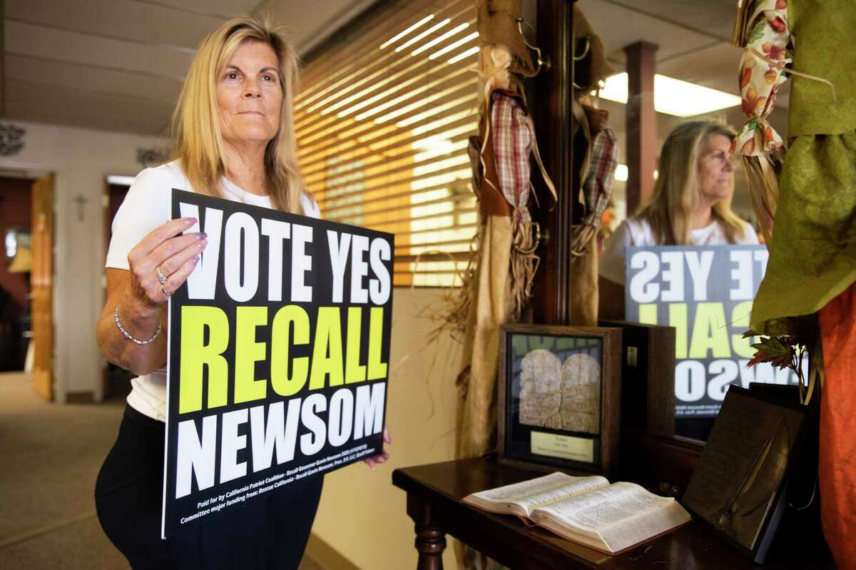 Jennifer Chavez-Ochoa holds a sign she still displays at her husband's Calaveras County law office in Valley Springs.