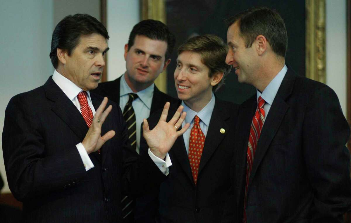 Texas Gov. Rick Perry, left, talks with, from left, Rep. Brandon Creighton, R-Conroe; Rep. Tan Parker, R-Flower Mound; and Rep. Jim Murphy, R-Houston, in the Texas House of Representatives Thursday, March 29, 2007, in Austin, Texas. The three are freshmen in the House.