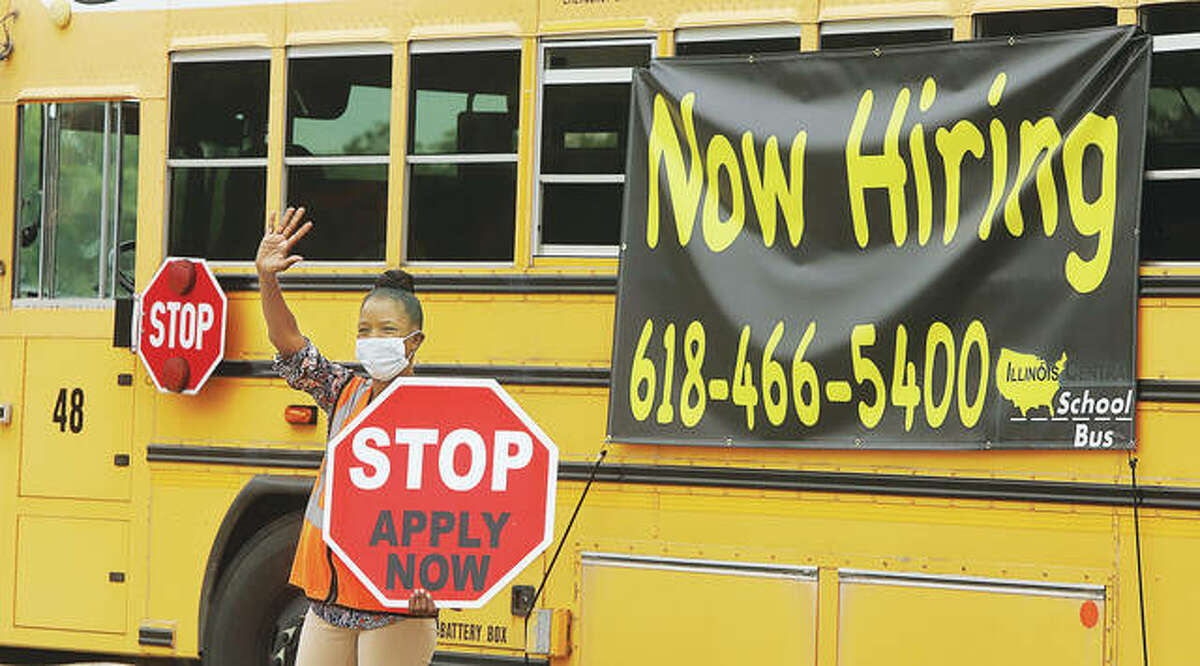 School bus driver Linda Lenoir was at State House Square in Alton Monday waving to passing motorists with bus monitor Linda North. Illinois Central School Bus is experiencing driver shortages like many other places across the country.